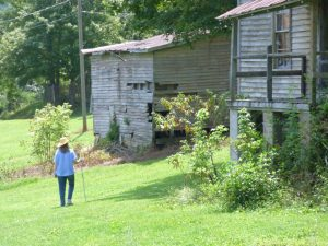 Beth walking on grass through abandoned homes and buildings at NC mill village