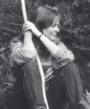 Beth sitting in the woods of New Hampshire holding a beaver stick