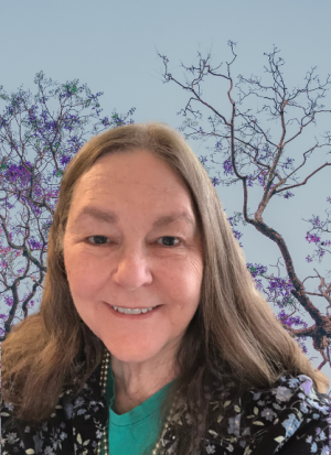 Beth smiling portrait in front of trees with purple blossoms