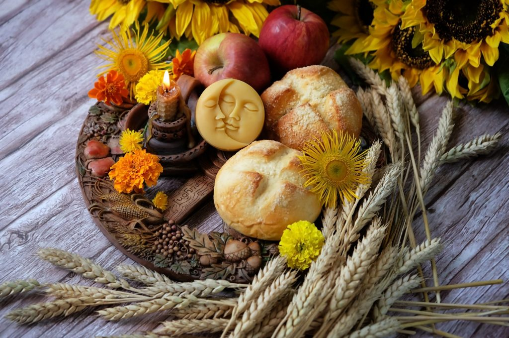 altar photo with break, flowers, apples, a candle, and stems of wheat