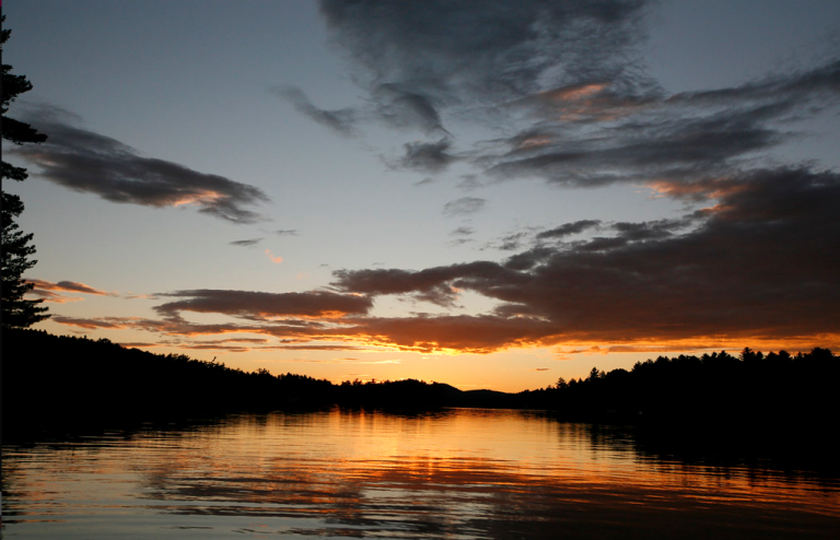 color photograph sunset over pine river pond lake in new hampshire